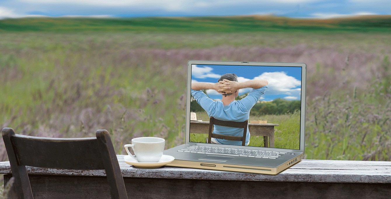 table with computer sitting in a field with a picture of a man sitting at that table in the field